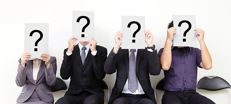 People seated with question marks covering their faces