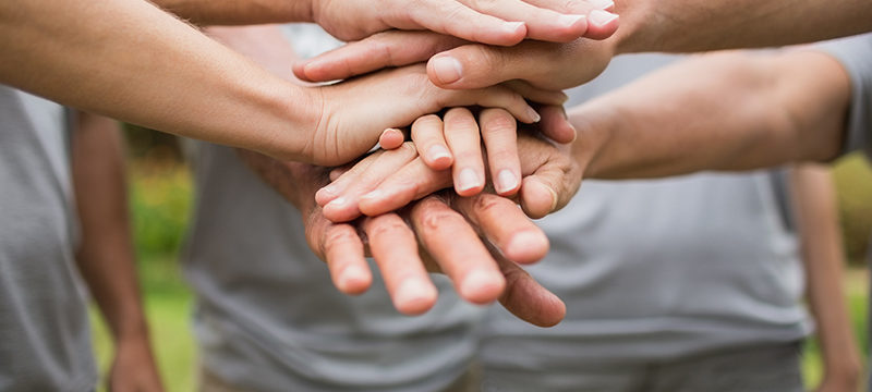 Hands placed on top of each other representing care and compassion